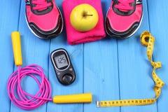 Glucometer, zapatos del deporte, manzana fresca y accesorios para la aptitud en tableros azules, espacio de la copia para el text Fotografía de archivo