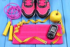 Glucometer, zapatos del deporte, manzana fresca y accesorios para la aptitud en tableros azules, espacio de la copia para el text Imagen de archivo