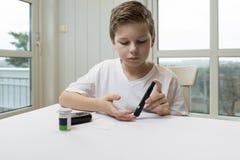 Glucosa de la medida del muchacho o suger de la sangre imagenes de archivo
