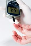 Glucose level blood test. Diabetic is doing a glucose level finger blood test Royalty Free Stock Photography