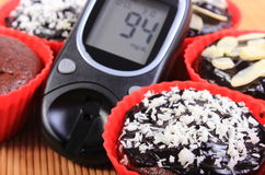 Glucose meter and chocolate muffins in red cups Royalty Free Stock Photos