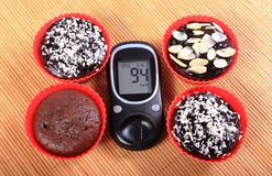 Glucose meter and chocolate muffins in red cups Stock Photography