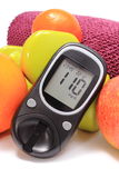 Glucose meter, fresh fruits and dumbbells with purple towel Royalty Free Stock Images
