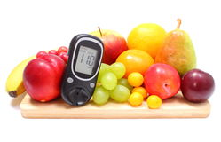 Glucose meter and fresh fruits on wooden cutting board Stock Images