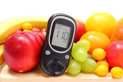 Glucose meter and fresh fruits on wooden cutting board Royalty Free Stock Photos