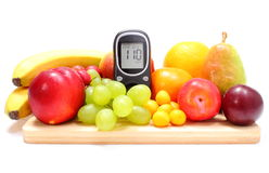 Glucose meter and fresh fruits on wooden cutting board Royalty Free Stock Image