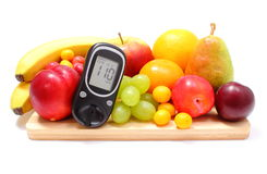 Glucose meter and fresh fruits on wooden cutting board Royalty Free Stock Images