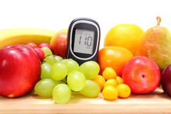 Glucose meter and fresh fruits on wooden cutting board Stock Image