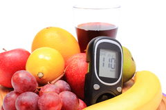 Glucose meter, fresh natural fruits and glass of juice Royalty Free Stock Photos