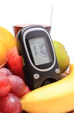 Glucose meter, fresh natural fruits and glass of juice Stock Image