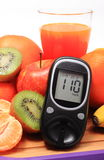 Glucose meter, fresh natural fruits and glass of juice Royalty Free Stock Images