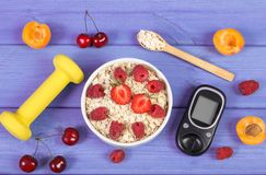 Glucometer for measuring sugar level, oatmeal with fruits and dumbbells, concept of diabetes and healthy lifestyle. Glucose meter, fresh oat flakes with fruits Stock Photo