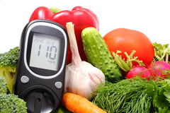 Glucose meter and fresh vegetables Stock Photos