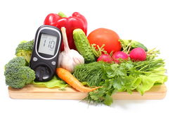 Glucose meter and fresh vegetables on wooden cutting board. Glucose meter and fresh ripe raw vegetables lying on wooden cutting board, desk of healthy organic Stock Photo