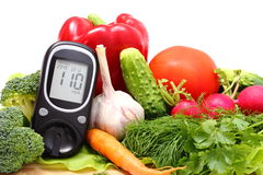 Glucose meter and fresh vegetables on wooden cutting board. Glucose meter and fresh ripe raw vegetables lying on wooden cutting board, desk of healthy organic Stock Photos