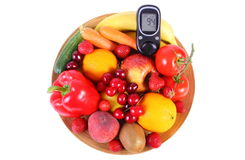 Glucose meter with fruits and vegetables on wooden plate Royalty Free Stock Photography