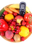 Glucose meter with fruits and vegetables on wooden plate Stock Photography