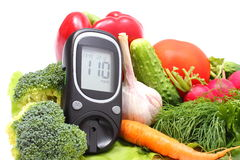 Glucose meter for glucose level and fresh vegetables on wooden cutting board. Glucose meter and fresh ripe raw vegetables lying on wooden cutting board, desk of Stock Photography
