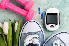 Glucose meter, gumshoes, pink dumbbells. Close up of glucose meter, gumshoes, pink dumbbells and white tulips on blue concerte background Stock Photos