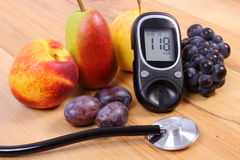Glucose meter with medical stethoscope and fresh fruits, healthy lifestyle Stock Image