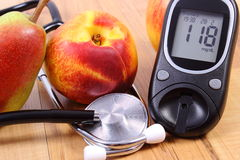 Glucose meter with medical stethoscope and fresh fruits, healthy lifestyle Royalty Free Stock Image