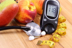 Glucose meter with medical stethoscope and fresh fruits, healthy lifestyle Stock Photos
