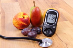 Glucose meter with medical stethoscope and fresh fruits, healthy lifestyle Stock Photo