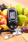 Glucose meter with medical stethoscope, fruits and dumbbells for using in fitness Royalty Free Stock Photos