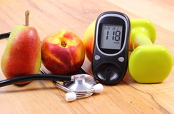Glucose meter with medical stethoscope, fruits and dumbbells for using in fitness Royalty Free Stock Images