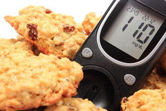 Glucose meter and oatmeal cookies on white background Royalty Free Stock Photos