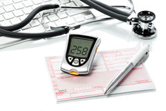 Glucose meter and recipe on the  doctors desk Stock Photography