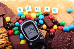 Glucose meter, sweets and cane brown sugar with word sugar, unhealthy food Royalty Free Stock Photos