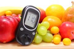 Glucosemeter en verse vruchten op houten scherpe raad Stock Fotografie