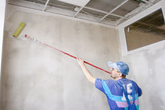 Glue. Master inflicts layer a glue for wallpaper on wall Stock Photography