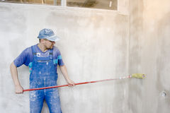 Glue. Master inflicts layer a glue for wallpaper on wall Stock Image