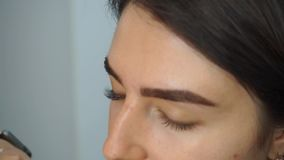 Glue artificial eyelashes. Eyelash extensions, the make-up artist takes with the help of forceps and imposes artificial eyelashes on the woman`s eyes. The stock video footage