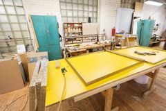 Glue gun and frame on workbench at workshop Stock Photos