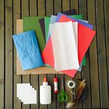 Papers and art craft material on slatted dark wood table. Glue, scissors, colored papers, feathers and tape on gray wood Royalty Free Stock Photos