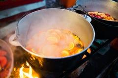 Gluhwein caliente o vino reflexionado sobre en una caldera en la invitación, caliente justo, local y picante Una bebida tradicion imagenes de archivo