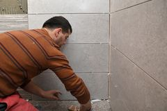Gluing tiles on the wall. Laying tiles on the wall. Worker installing big ceramic tiles on the walls stock image