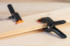 Gluing Wood. Two Plastic Spring Clamps Joining Two Pieces Of Woo Stock Photography