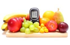 Glukosemeter und frische Früchte auf hölzernem Schneidebrett Lizenzfreies Stockbild