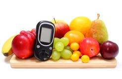 Glukosemeter und frische Früchte auf hölzernem Schneidebrett Lizenzfreie Stockbilder