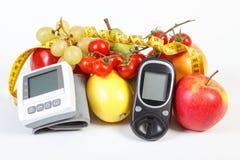 Glukosmeter, blodtryckbildskärm, frukter med grönsaker och cm, sund livsstil Fotografering för Bildbyråer