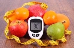 Glukosmeter med måttband och nya frukter, sockersjuka, sund näring och bantningbegrepp Arkivbilder