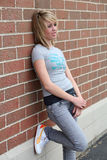Glum. Pretty blonde teen leaning against brick wall looking distressed Stock Photo