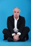 Glum businessman. Sat on the floor Royalty Free Stock Photo