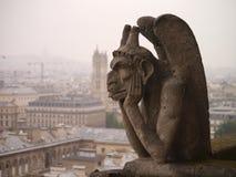 A Glum Gargoyle on a misty Paris morning. A Gargoyle at Notre Dame over Paris, France Royalty Free Stock Images