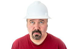 Glum looking workman looking for inspiration. Glum looking workman wearing a hardhat looking for inspiration raising his eyes to the heavens in supplication Royalty Free Stock Photography