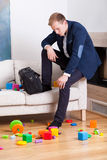 Glum man sitting on sofa. In dirty living room Stock Images